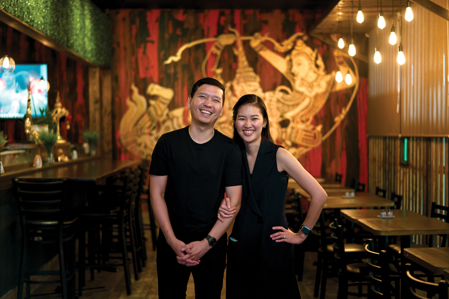 Varut and Kathy Hansapiromchak in front of a custom mural by a celebrated Bangkok artist. Photo by Wyatt Kostygan.