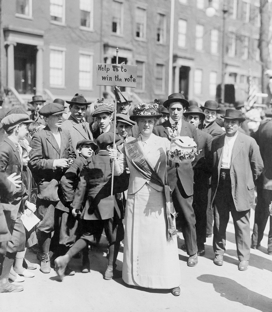 Women identified as Mrs. Suffern, is surrounded by a crowd of men and boys, while she holds a home-made banner in women suffragist parade 'Help us to win the vote.' 1914.
