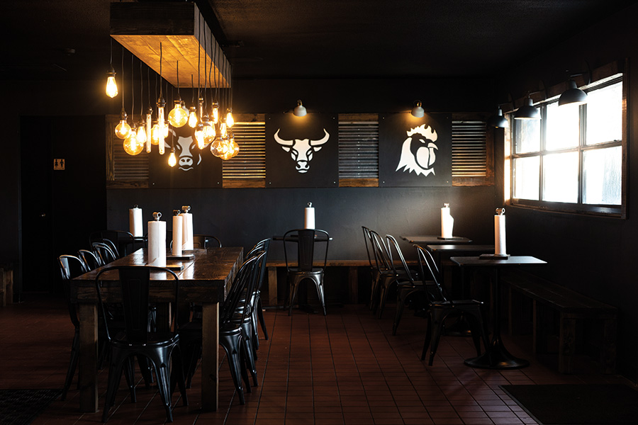Jet black  interior walls paired with  gleaming black lacquered chairs set a sophisticated edge to this BBQ joint.Photography by Wyatt Kostygan